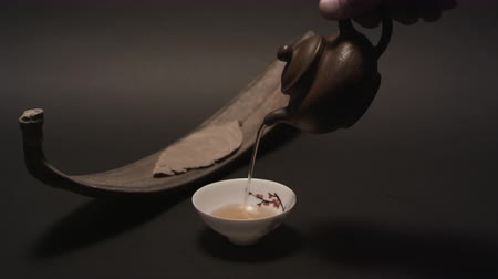 papyrus : Pouring Chinese tea into a cup from a traditional Yixing clay teapot Stock Footage