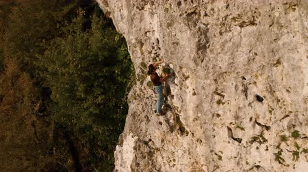 A rock climber climbs a category 5 route along a rock