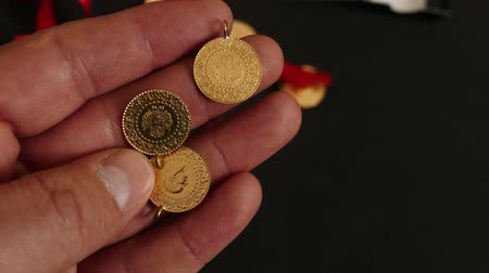hoard : a man has gold in his hand, Turkish republic quarter gold,Turkish republic quarter gold on black background. Stock Footage
