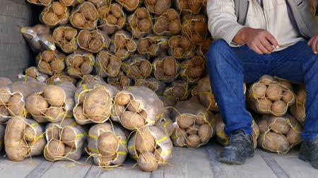 çuval bezi : farmer selling potatoes in large sacks, farmer selling large amounts of potatoes.