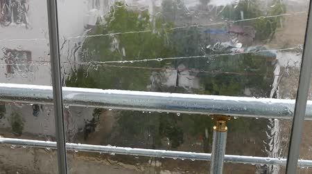 hail : heavy rain, rain falling on glass balcony and hail grains.