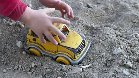playing with a child in the soil, child playing in the soil with toy car.