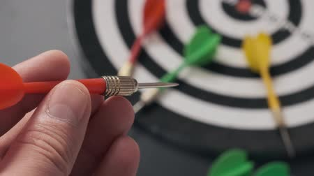 gra planszowa : Read in the hands of a man taking aim with green darts, dart board and darts, Wideo