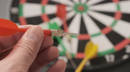 dart : Read in the hands of a man taking aim with green darts