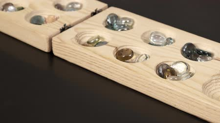 захват : wooden mangala game, mangala game board and glass marbles, on black background
