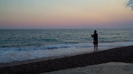rákos : man fishing on the beach at sunset