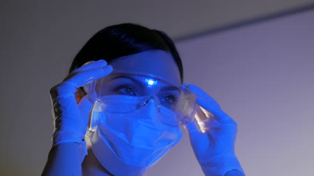 latex gloves : Close up video of a young brunette nurse at the mask wears protective goggles