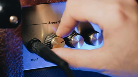 amplificador : Mens hands twist tumblers on control panel of guitar amplifier. A mode switch being switches on amp. Mans hand inserts cable jack in guitar amp