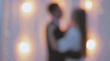 latino americana : Newlyweds Silhouettes dancing against a white wall with lights at night. Blurred video, beautiful background. 4k