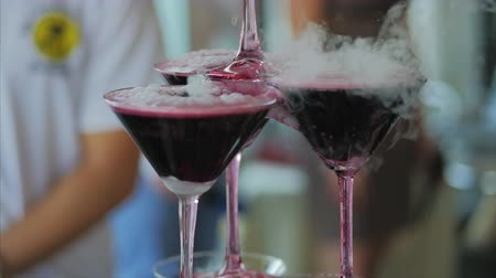 pour out : Waiter pouring red wine or champagne into glasses with liquid nitrogen for party. Young man pours wine into the pyramid from the glasses.