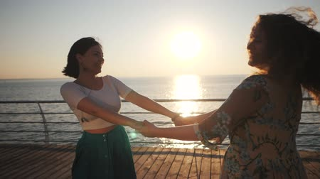 két : Beautiful girls whirling, dancing and playing on the embankment near sea or ocean. Friendship concept, slow motion
