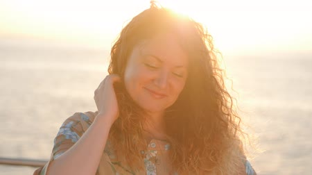 kudrnatý : Portrait of young attractive woman with curly red hair standing near sea or ocean in sunrise or sunset light. The girl looks at the camera, then straightens her hair and looks at the sun. Slow motion.