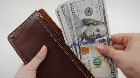 cüzdan : Top view of a woman counting and Takes out dollars from her brown leather wallet. Female holds purse against wooden background. Slow motion.