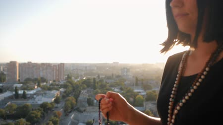 mala : Female lit hand close up on sunset or sunrise, counts Malas strands of gemstones beads used for keeping count during mantra meditations. Woman sits on top above city. Slow motion. Vídeos