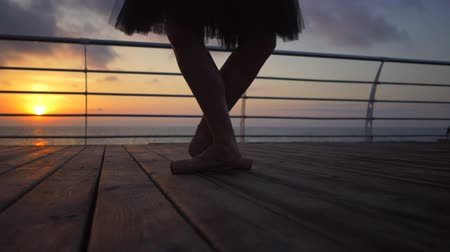 kültürlü : Close up of a ballet dancers feet as she practices pointe exercises on the embankment near sea or ocean, sunrise background, Silhouette of womans feet in pointe shoes. Ballerina shows classic ballet pas. Slow motion. Stok Video