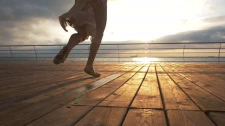 premier : Young ballerina in beige silk dress running in pointe shoes on wooden embankment to sea or ocean. Sunrise background. Slow motion. Stock Footage