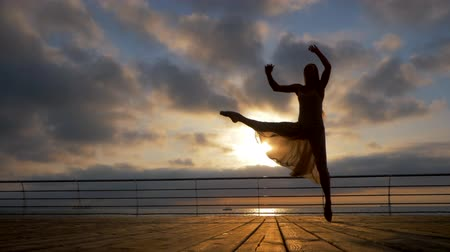 bale : Jumping ballerina in beige silk dress and pointe on embankment above ocean or sea beach at sunrise or sunset. Silhouette of young beautiful blonde woman with long hair practicing stretching and classic exercises. Epic jump. SLOW MOTION.