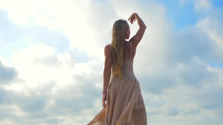 balerína : Beautiful scene of a dancing ballerina in beige silk dress and pointe on sand beach near ocean or sea beach at sunrise or sunset. Young beautiful blonde sensual woman with long hair practicing stretching and classic exercises. SLOW MOTION. Dostupné videozáznamy