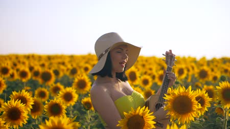 double happiness : Happy woman in sunflower field playing on ukulele and singing. Summer girl in cowboy straw hat. Caucasian young lady have fun. Slow motion. Little guitar. music concept.