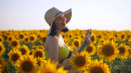 hint : Happy woman in sunflower field playing on ukulele and singing. Summer girl in cowboy straw hat. Caucasian young lady have fun. Slow motion. Little guitar. music concept.
