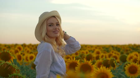 outside : Young beautiful blonde woman standing in sunflower field. Sunset background. Sexy sensual portrait of girl in straw hat and white summer dress. Slow motion. Stock Footage
