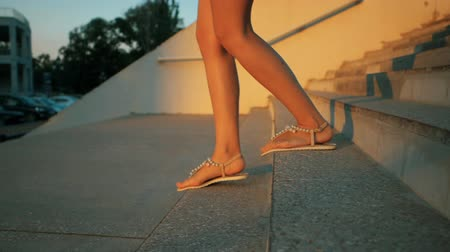 boldness : Woman legs in fashionable sandals going down the stairs outrdoor. Slow motion. Summertime Stock Footage