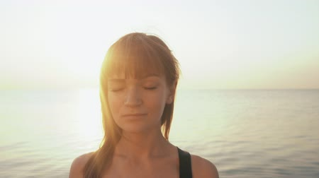 pozisyon : Young caucasian woman in bodysuit relaxing by practicing yoga on the beach near calm sea, close-up of hands, gyan mudra and lotus position. Sunrise background. Slow motion. Stok Video