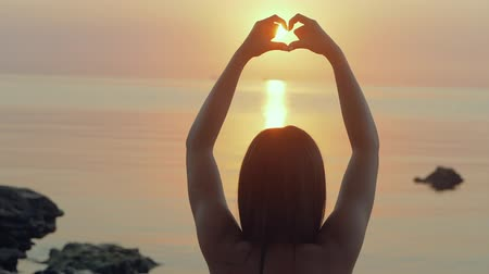 ve tvaru : Young woman shapes heart with hands over the sunset by the ocean. Slow motion.