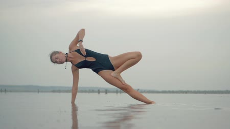 remo : Young caucasian woman in swimsuit practicing yoga in water liman, lake or river. Beautiful reflection. Complex asanas, balance. Fitness, sport, yoga and healthy lifestyle concept. Slow motion.