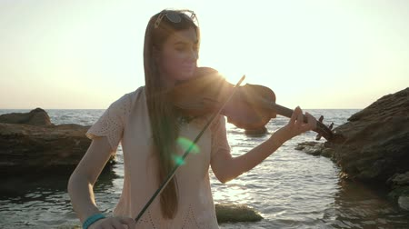 sentimentos : Young beautiful caucasian girl wearing jeans plays violin staying on the beach near the beautiful sea or ocean, Slow motion.