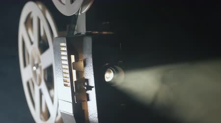 sökülmüş : Front view of an old-fashioned antique Super 8mm film projector, projecting a beam of light in a dark room next to a stack of unraveled film reels.