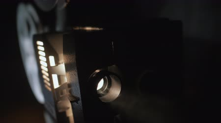 sökülmüş : Front view of old-fashioned antique Super 8mm film projector,projecting beam of light in dark room next to stack of unraveled film reels.vintage theater spot light on black curtain with dust floating Stok Video