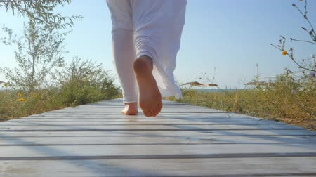 отдыха : Legs of caucasian girl wearing white long dress and silver bracelets walking on white wooden floor to sea beach, sun, lens, flare. Slow motion. Woman walks away camera