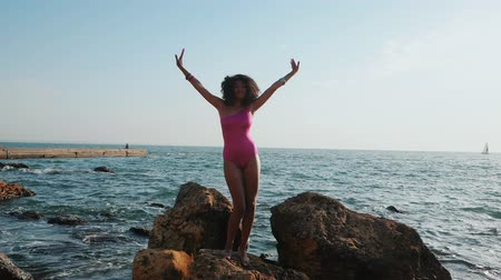 afro amerikai : Portrait of black people, pretty happy young african american woman dancing and smiling. Sexy girl in pink swimsuit and jewelry performs on the beach. Beautiful, silhouetted lady. Slow motion.