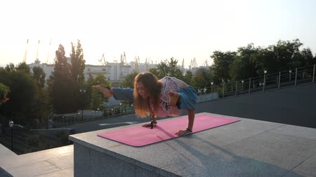 mala : Young beautiful caucasian woman doing yoga asana in the city. Summer morning. Girl wearing blue pants, pink lace t-shirt and mala beads for meditation. Slow motion. Vídeos