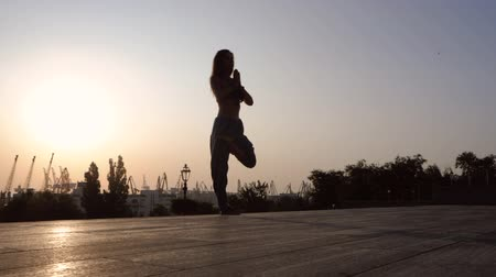 mala : Young beautiful caucasian woman doing yoga asana on stairs in the city. Summer morning. Girl wearing blue pants, black top and mala beads for meditation. Surya Namaskar. Slow motion.
