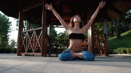 posição : Morning yoga portrait of beautiful young woman in blue pants and top. Health care concept. Girls meditation on wooden alcove background in park at summer. Slow motion.
