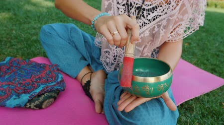 исцелять : Woman playing singing bowl while sitting on pink yoga mat in park at summer. Vintage tonned. Beautiful girl with mala beads meditating on green grass. Slow motion.