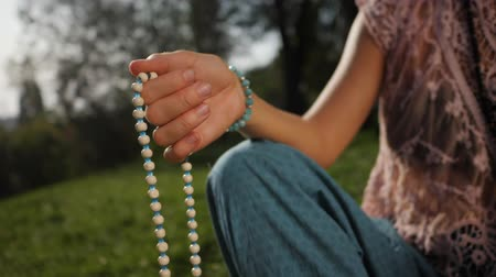 mala : Woman, lit hand close up, counts Malas, strands of wooden beads used for keeping count during mantra meditations. Buddhism. Girl sitting in the park at summer. Slow motion
