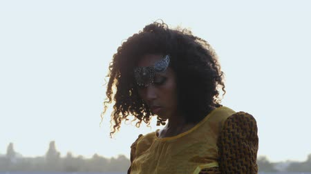 черные волосы : Portrait of young afro-american gypsy woman in colorful yellow traditional dress and silver crown on forehead smiling and posing close to camera. Sexy fashion girl with curly hair outdoor in slow motion.