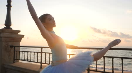 rusya : Ballerina in blue ballet tutu and point on embankment above ocean or sea at sunrise. Young beautiful brunette woman practicing stretching and exercises. SLOW MOTION. Close up view,