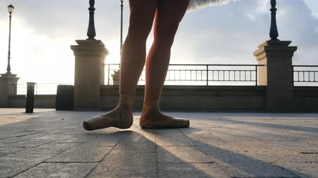 kültürlü : Close up of a ballet dancers feet as she practices pointe exercises on the stone embankment. Womans feet in pointe shoes. Ballerina shows classic ballet pas. Slow motion. Flare, gimbal shot Stok Video