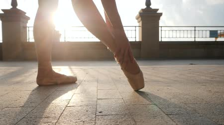 kültürlü : Close up of a ballet dancers feet as she corrects pointe on the stone embankment. Womans feet in pointe shoes. Ballerina preparing for classic ballet pas. Slow motion. Flare, gimbal shot