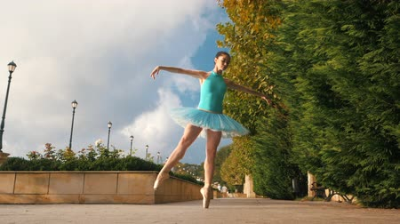 balerína : Dancing ballerina in blue ballet tutu and point on european street with trees in summer. Young beautiful brunette woman practicing stretching and exercises. SLOW MOTION. Flare, overall plan Dostupné videozáznamy