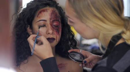 ведьма : Make-up artist make the girl halloween make upin studio.Halloween face art.Woman applies on professional greasepaint on the face of spanish girl.War-paint with blood, scars and wounds.Slow motion.