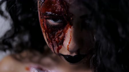 luxúria : Scary portrait of young girl with Halloween blood makeup. Beautiful latin woman with curly hair looking into camera in studio. Living dead greasepaint. Slow motion.