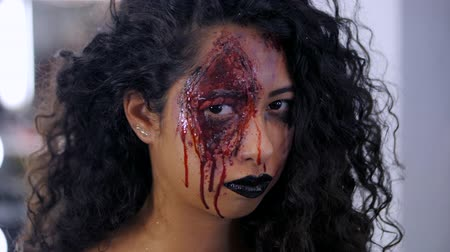 luxúria : Scary portrait of young girl with Halloween blood makeup. Beautiful latin woman with curly hair looking into camera. Slow motion. Stock Footage