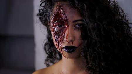 wampir : Scary portrait of young zombie girl with Halloween blood makeup. Beautiful latin woman with curly hair looking into camera in studio. Slow motion.