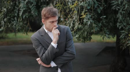 определенный : Portrait of young successful pensive businessman in the city. Man in a business suit in the autumn street. Slow motion. Handsome person ponders about work Стоковые видеозаписи