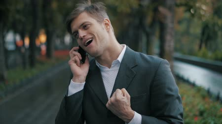 ouvido : Young handsome businessman talking on mobile phone in the city. Guy heard good news and he is happy. Success concept. The joy of speaking on the phone. Slow motion.